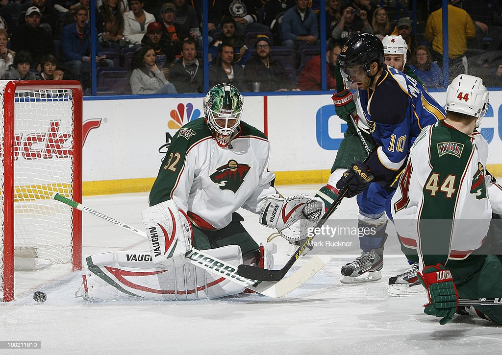 Niklas Backstrom #32 of the Minnesota Wild just gets a piece of a shot from Andy McDonald #10 of the St. Louis Blues in an NHL game on January 27, 2013 at Scottrade Center in St. Louis, Missouri.
