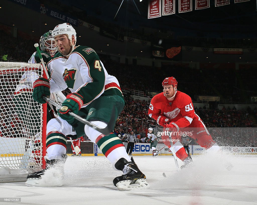 Niklas Backstrom #32 of the Minnesota Wild watches over his shoulder as teamate Clayton Stoner #4 and Johan Franzen #93 of the Detroit Red Wings go behind the net for the puck during a NHL game at Joe Louis Arena on March 20, 2013 in Detroit, Michigan.