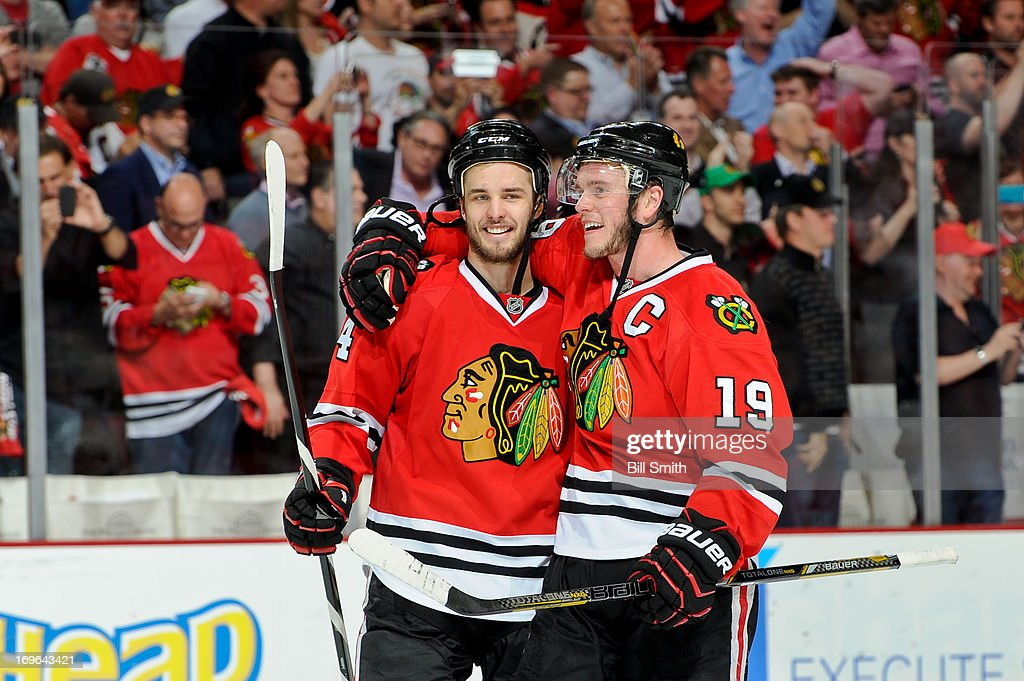 Niklas Hjalmarsson and Jonathan Toews of the Chicago Blackhawks celebrate after the Blackhawks defeated the Detroit Red Wings 21 to win the series in...