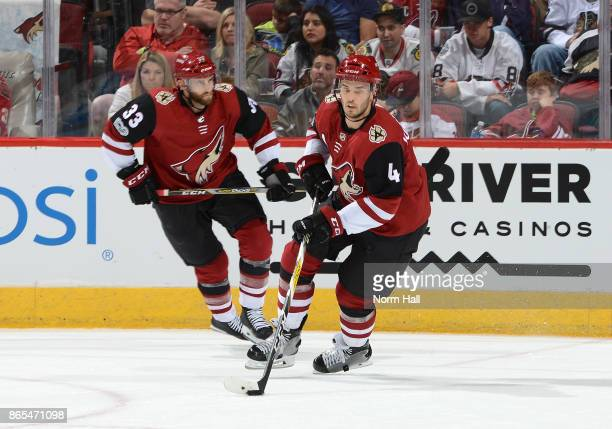 Niklas Hjalmarsson of the Arizona Coyotes skates the puck up ice with teammate Alex Goligoski against the Chicago Blackhawks at Gila River Arena on...