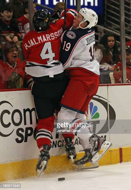 Niklas Hjalmarsson of the Chicago Blackhawks and Ryan Johansen of the Columbus Blue Jackets collide against the boards at the United Center on...