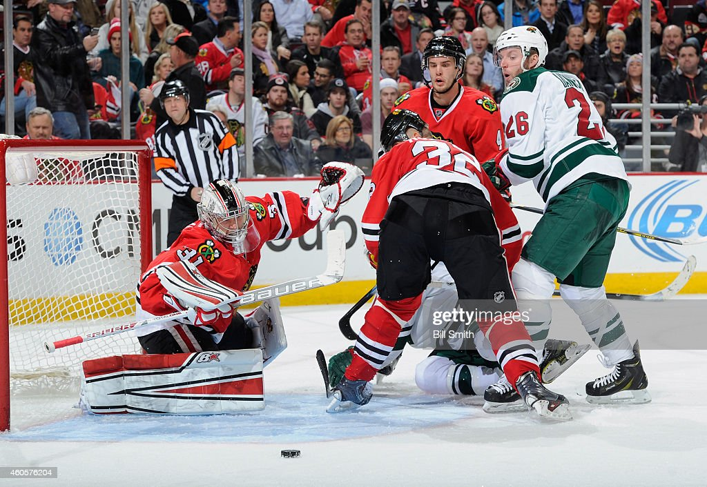 Niklas Hjalmarsson #4 of the Chicago Blackhawks and Thomas Vanek #26 of the Minnesota Wild watch as the puck approaches goalie Antti Raanta #31 during the NHL game at the United Center on December 16, 2014 in Chicago, Illinois.