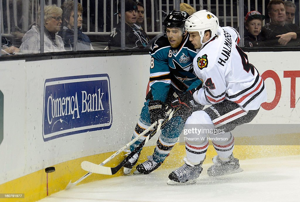 Niklas Hjalmarsson #4 of the Chicago Blackhawks battles for control of the buck with Joe Pavelski #8 of the San Jose Sharks at HP Pavilion on February 5, 2013 in San Jose, California.