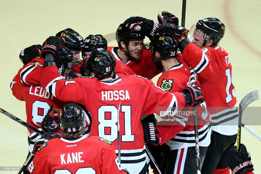 Niklas Hjalmarsson #4 of the Chicago Blackhawks celebrates with his teammates after Andrew Shaw #65 (not pictured) scored the game-winning goal in the third overtime against goalie Tuukka Rask #40 of the Boston Bruins to give the Bruins a 4-3 win in Game One of the NHL 2013 Stanley Cup Final at United Center on June 12, 2013 in Chicago, Illinois.