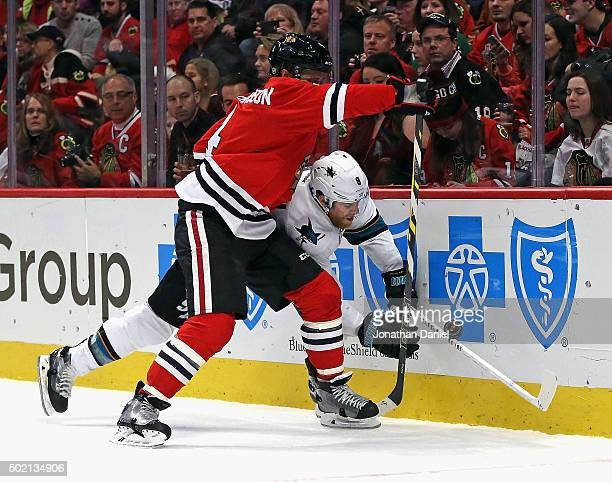 Niklas Hjalmarsson of the Chicago Blackhawks checks Dainius Zubrus of the San Jose Sharks into the boards at the United Center on December 20 2015 in...