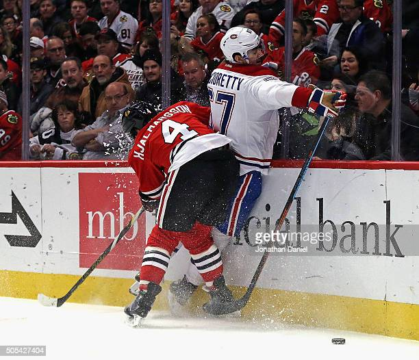 Niklas Hjalmarsson of the Chicago Blackhawks checks Max Pacioretty of the Montreal Canadiens into the boards at the United Center on January 17 2016...