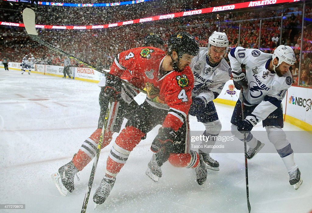 <a gi-track='captionPersonalityLinkClicked' href=/galleries/search?phrase=Niklas+Hjalmarsson&family=editorial&specificpeople=2006442 ng-click='$event.stopPropagation()'>Niklas Hjalmarsson</a> #4 of the Chicago Blackhawks fights for the puck against <a gi-track='captionPersonalityLinkClicked' href=/galleries/search?phrase=Jonathan+Drouin+-+Ice+Hockey+Player&family=editorial&specificpeople=10884241 ng-click='$event.stopPropagation()'>Jonathan Drouin</a> #27 and <a gi-track='captionPersonalityLinkClicked' href=/galleries/search?phrase=Brenden+Morrow&family=editorial&specificpeople=202256 ng-click='$event.stopPropagation()'>Brenden Morrow</a> #10 of the Tampa Bay Lightning in the first period during Game Six of the 2015 NHL Stanley Cup Final at the United Center on June 15, 2015 in Chicago, Illinois.