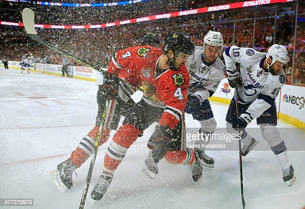 Niklas Hjalmarsson of the Chicago Blackhawks fights for the puck against Jonathan Drouin and Brenden Morrow of the Tampa Bay Lightning in the first...