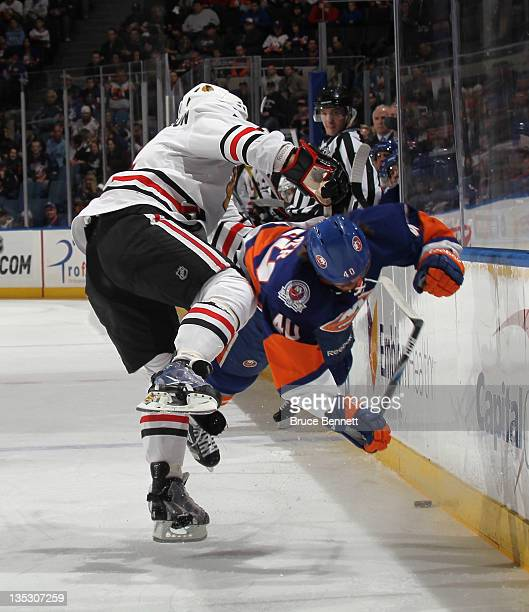 Niklas Hjalmarsson of the Chicago Blackhawks hits Michael Grabner of the New York Islanders during the first period at the Nassau Veterans Memorial...