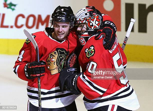 Niklas Hjalmarsson of the Chicago Blackhawks hugs Corey Crawford after Crawford shut out the Edmonton Oilers at the United Center on December 17 2015...
