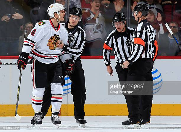 Niklas Hjalmarsson of the Chicago Blackhawks protests with linesman Kiel Murchison referee Brad Watson and referee Chris Lee after being penalized...