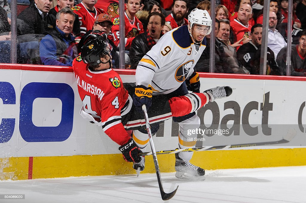 Niklas Hjalmarsson #4 of the Chicago Blackhawks takes a hard hit from Evander Kane #9 of the Buffalo Sabres in the third period of the NHL game at the United Center on January 8, 2016 in Chicago, Illinois. The Chicago Blackhawks defeated the Buffalo Sabres 3 to 1.