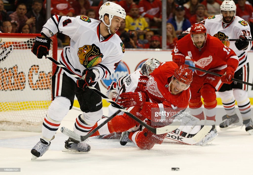Niklas Hjalmarsson #4 of the Chicago Blackhawks tries to get the puck past the diving Justin Abdelkader #8 of the Detroit Red Wings during the second period in Game Four of the Western Conference Semifinals during the 2013 NHL Stanley Cup Playoffs at Joe Louis Arena on May 23, 2013 in Detroit, Michigan.