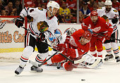 Niklas Hjalmarsson of the Chicago Blackhawks tries to get the puck past the diving Justin Abdelkader of the Detroit Red Wings during the second...