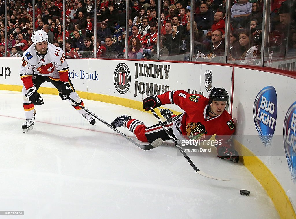 Niklas Hjalmarsson of the Chicago Blackhawks tries to reach the puck after being knocked down by Brian McGrattan of the Calgary Flames at the United...
