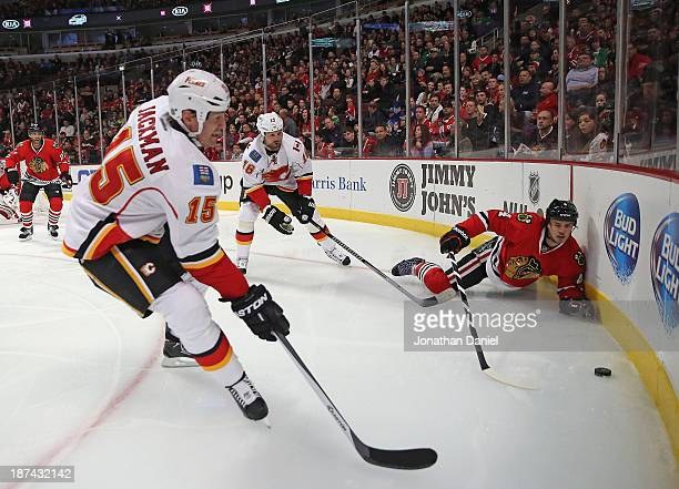 Niklas Hjalmarsson of the Chicago Blackhawks tries to reach the puck after being knocked down by Brian McGrattan of the Calgary Flames as Tim Jackman...