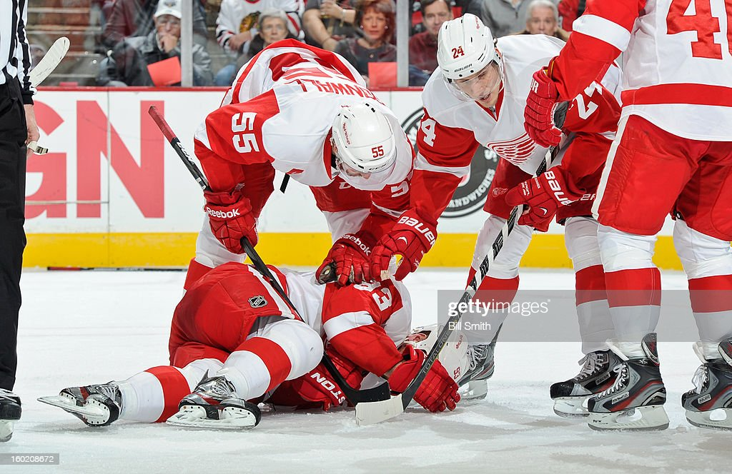Niklas Kronwall #55 and Damien Brunner #24 of the Detroit Red Wings check on teammate Johan Franzen #93, after Franzen was hit by Jamal Mayers #22 of the Chicago Blackhawks, during the NHL game on January 27, 2013 at the United Center in Chicago, Illinois.