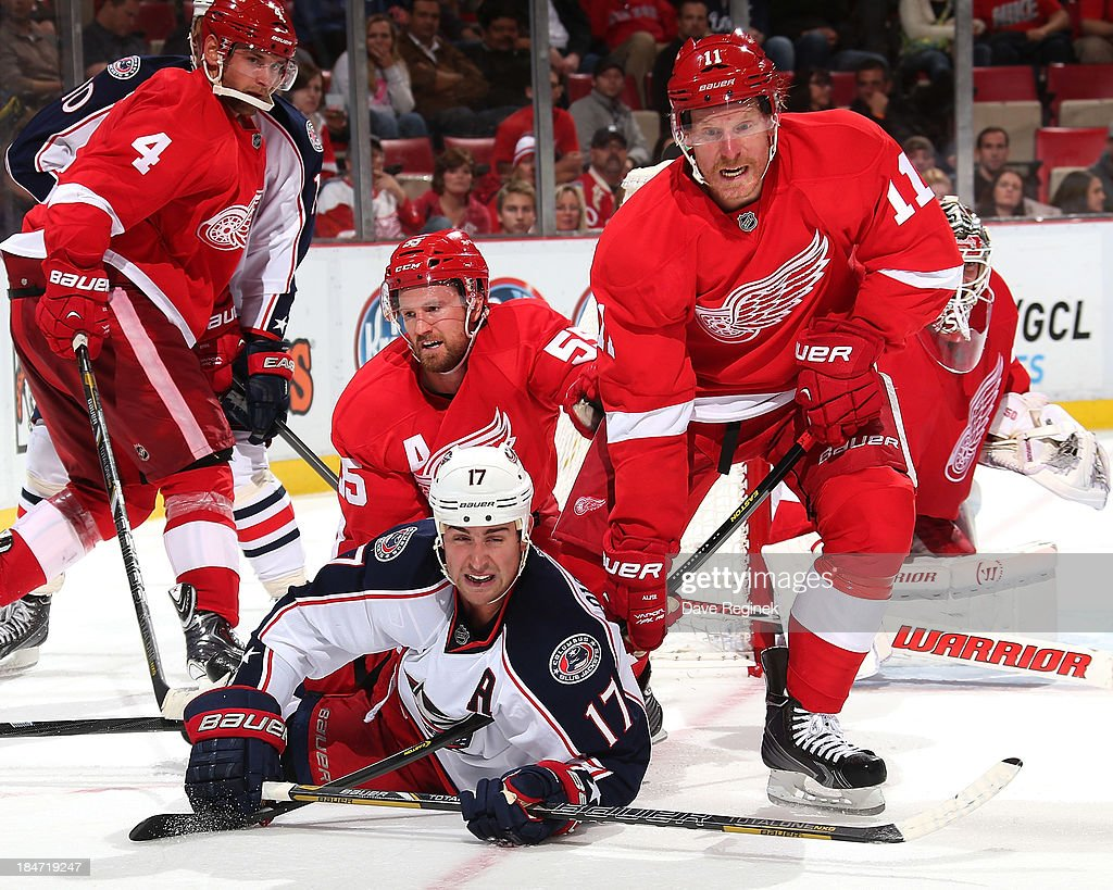 Niklas Kronwall #55 and Daniel Alfredsson #11 of the Detroit Red Wings both take down Brandon Dubinsky #17 of the Columbus Blue Jackets at the side of the net during a NHL game at Joe Louis Arena on October 15, 2013 in Detroit, Michigan.