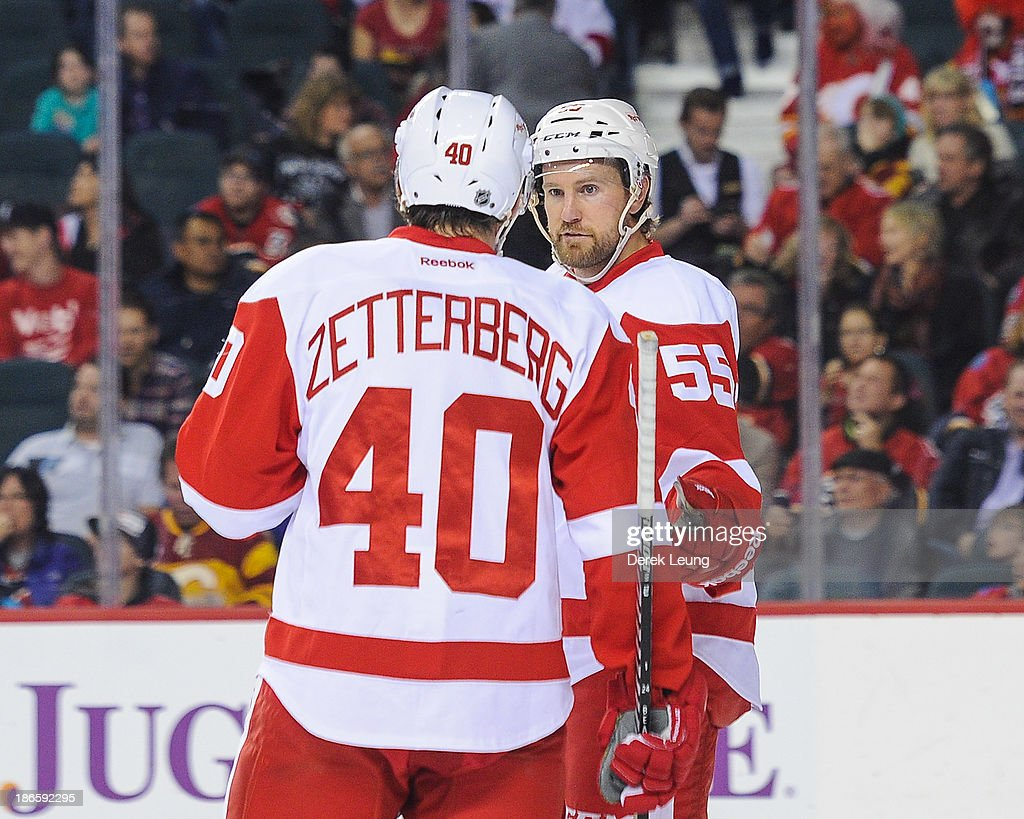 Niklas Kronwall #55 and Henrik Zetterberg #40 of the Detroit Red Wings confer between play against the Calgary Flames during an NHL game at Scotiabank Saddledome on November 1, 2013 in Calgary, Alberta, Canada.