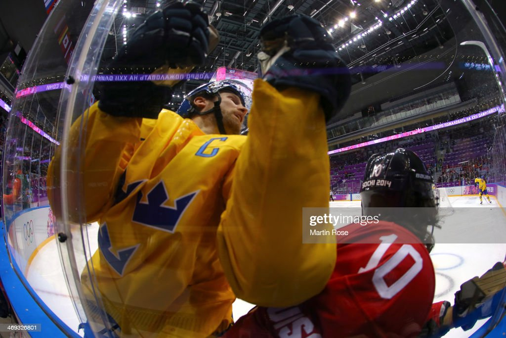 Niklas Kronwall #55 of Sweden and Andres Ambuhl #10 of Switzerland collide against the boards in the first period during the Men's Ice Hockey Preliminary Round Group C game on day seven of the Sochi 2014 Winter Olympics at Bolshoy Ice Dome on February 14, 2014 in Sochi, Russia.