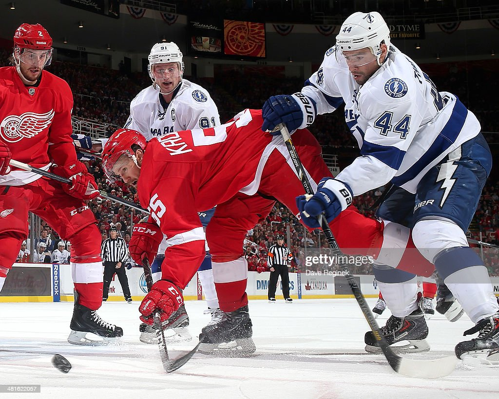 Niklas Kronwall of the Detroit Red Wings and Nate Thompson of the Tampa Bay Lightning battle for the puck to the side of the net during an NHL game...