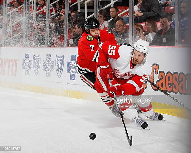 Niklas Kronwall of the Detroit Red Wings battles for the puck with Brent Seabrook of the Chicago Blackhawks during an NHL game at Joe Louis Arena on...