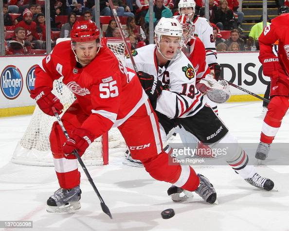 Niklas Kronwall of the Detroit Red Wings battles for the puck with Jonathan Toews of the Chicago Blackhawks during an NHL game at Joe Louis Arena on...