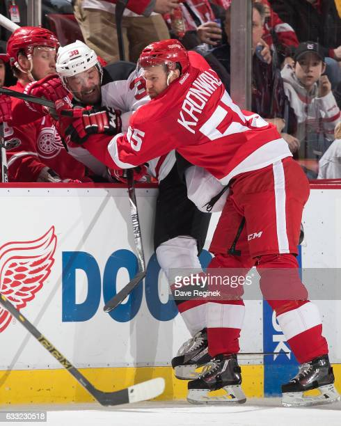 Niklas Kronwall of the Detroit Red Wings checks Vernon Fiddler of the New Jersey Devils into the bench during an NHL game at Joe Louis Arena on...