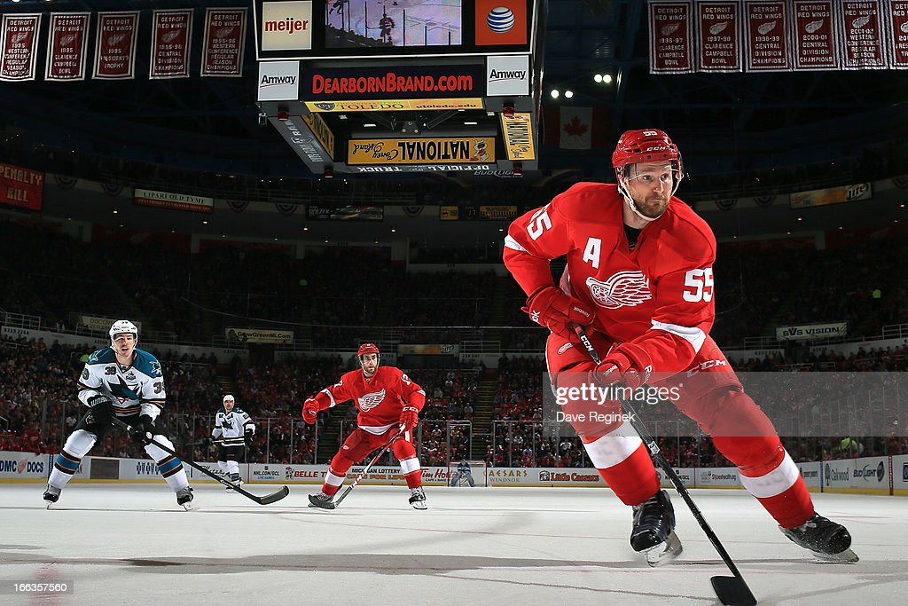 <a gi-track='captionPersonalityLinkClicked' href=/galleries/search?phrase=Niklas+Kronwall&family=editorial&specificpeople=220826 ng-click='$event.stopPropagation()'>Niklas Kronwall</a> #55 of the Detroit Red Wings goes into the corner for the puck as teamate Patrick Eaves #17 shadows <a gi-track='captionPersonalityLinkClicked' href=/galleries/search?phrase=Logan+Couture&family=editorial&specificpeople=809700 ng-click='$event.stopPropagation()'>Logan Couture</a> #39 of the San Jose Sharks during a NHL game at Joe Louis Arena on April 11, 2013 in Detroit, Michigan. San Jose defeated Detroit 3-2 in a shoot-out
