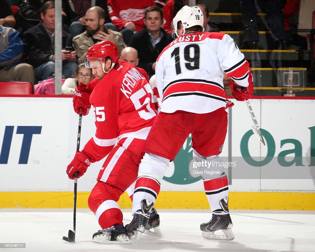 <a gi-track='captionPersonalityLinkClicked' href=/galleries/search?phrase=Niklas+Kronwall&family=editorial&specificpeople=220826 ng-click='$event.stopPropagation()'>Niklas Kronwall</a> #55 of the Detroit Red Wings handles the puck as <a gi-track='captionPersonalityLinkClicked' href=/galleries/search?phrase=Jiri+Tlusty&family=editorial&specificpeople=543236 ng-click='$event.stopPropagation()'>Jiri Tlusty</a> #19 of the Carolina Hurricanes puts a body on him during an NHL game at Joe Louis Arena on November 21, 2013 in Detroit, Michigan.