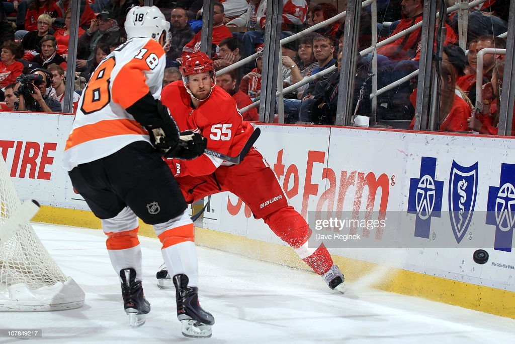 Niklas Kronwall #55 of the Detroit Red Wings sends the puck past Mike Richards #18 of the Philadelphia Flyers during an NHL game at Joe Louis Arena on January 2, 2011 in Detroit, Michigan.