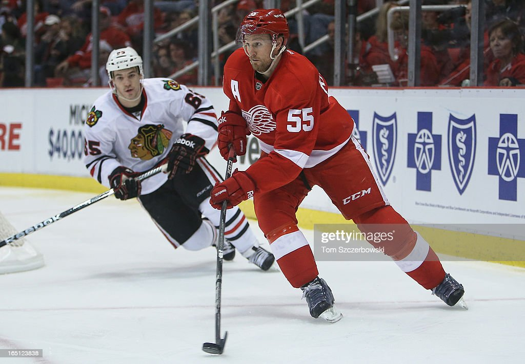 <a gi-track='captionPersonalityLinkClicked' href=/galleries/search?phrase=Niklas+Kronwall&family=editorial&specificpeople=220826 ng-click='$event.stopPropagation()'>Niklas Kronwall</a> #55 of the Detroit Red Wings skates out with the puck during an NHL game as Andrew Shaw #65 of the Chicago Blackhawks chases him at Joe Louis Arena on March 31, 2013 in Detroit, Michigan.