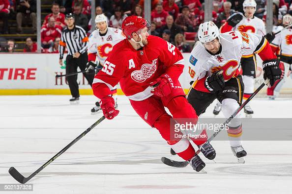 Niklas Kronwall of the Detroit Red Wings skates up ice in front of David Jones of the Calgary Flames during an NHL game at Joe Louis Arena on...