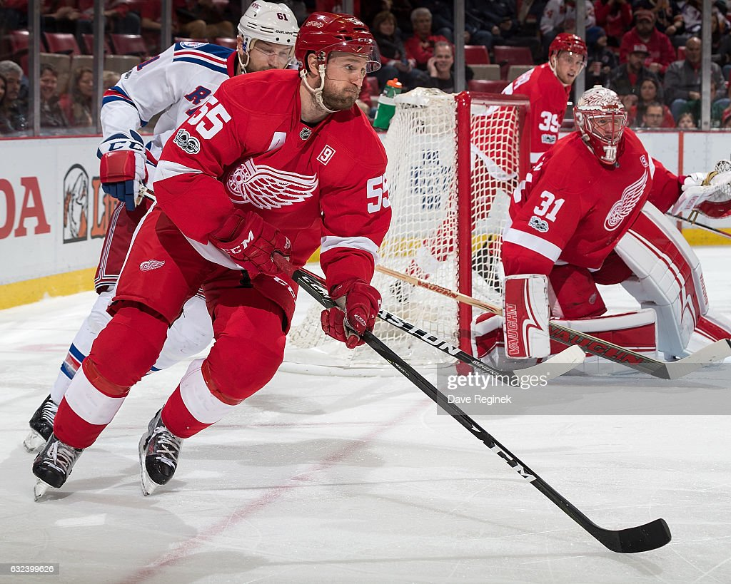 Niklas Kronwall #55 of the Detroit Red Wings skates with the puck past teammate goaltender Jared Coreau #31 followed by Rick Nash #61 of the New York Rangers during an NHL game at Joe Louis Arena on January 22, 2017 in Detroit, Michigan.