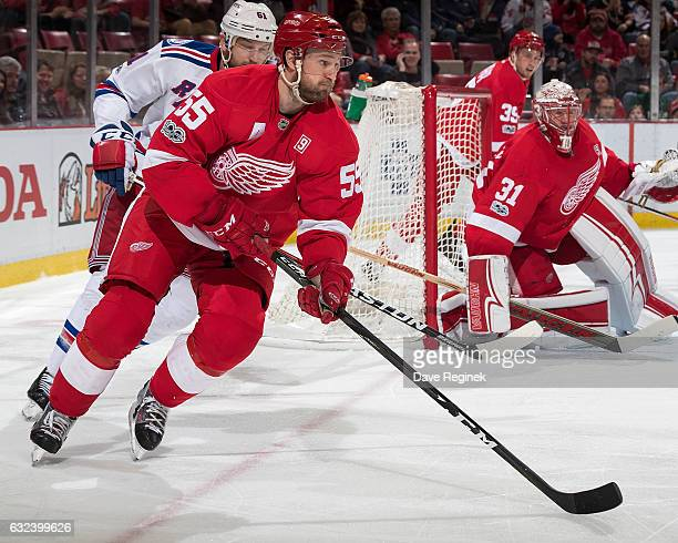 Niklas Kronwall of the Detroit Red Wings skates with the puck past teammate goaltender Jared Coreau followed by Rick Nash of the New York Rangers...