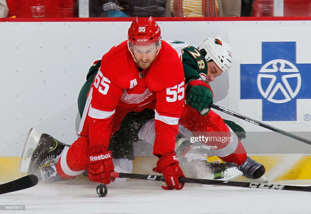 <a gi-track='captionPersonalityLinkClicked' href=/galleries/search?phrase=Niklas+Kronwall&family=editorial&specificpeople=220826 ng-click='$event.stopPropagation()'>Niklas Kronwall</a> #55 of the Detroit Red Wings tries to get control of the puck after checking <a gi-track='captionPersonalityLinkClicked' href=/galleries/search?phrase=Zenon+Konopka&family=editorial&specificpeople=2105876 ng-click='$event.stopPropagation()'>Zenon Konopka</a> #28 of the Minnesota Wild into the boards in the first period at Joe Louis Arena on January 25, 2013 in Detroit, Michigan.