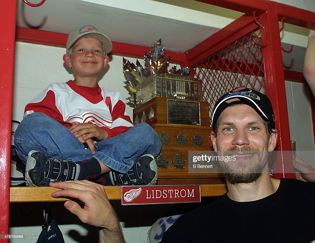 Niklas Lidstrom #5 of the Detroit Red Wings celebrates a Stanley Cup victory with his son and the Conn Smythe Trophy on June 14, 2002 at the Joe Louis Arena in Detroit, Michigan.