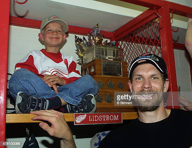 Niklas Lidstrom of the Detroit Red Wings celebrates a Stanley Cup victory with his son and the Conn Smythe Trophy on June 14 2002 at the Joe Louis...
