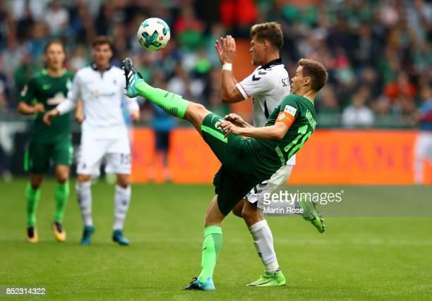 Niklas Moisander of Bremen and Florian Niederlechner of Freiburg battle for the ball during the Bundesliga match between SV Werder Bremen and...