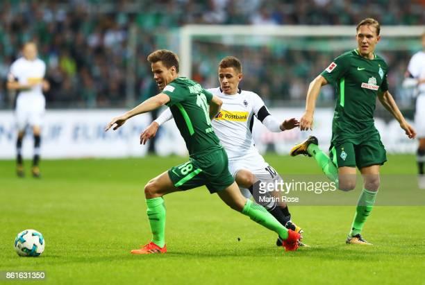 Niklas Moisander of Werder Bremen is challenged by Thorgan Hazard of Borussia Moenchengladbach during the Bundesliga match between SV Werder Bremen...