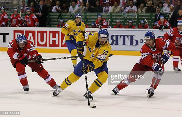 Niklas Persson of Sweden controls the puck against Jakub Voracek and Marek Zidlicky of Czech Republic during the IIHF World Championship semi final...