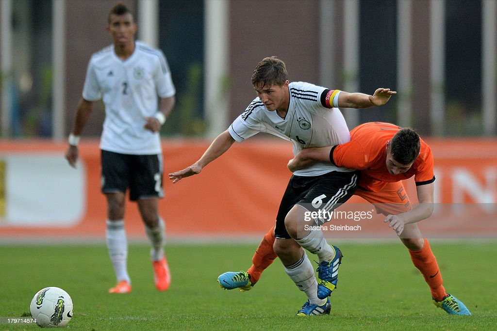 Niklas Stark of Germany is tackled by Sander Heesakkers (R) of The Netherlands during the U19 international friendly match between The Netherlands and Germany on September 6, 2013 in Nijmegen, Netherlands.