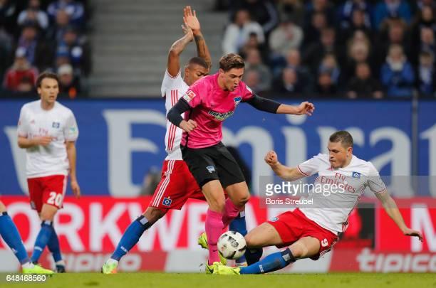 Niklas Stark of Hertha BSC is challenged by Kyriakos Papadopoulos of Hamburger SV and Walace of Hamburger SV during the Bundesliga match between...