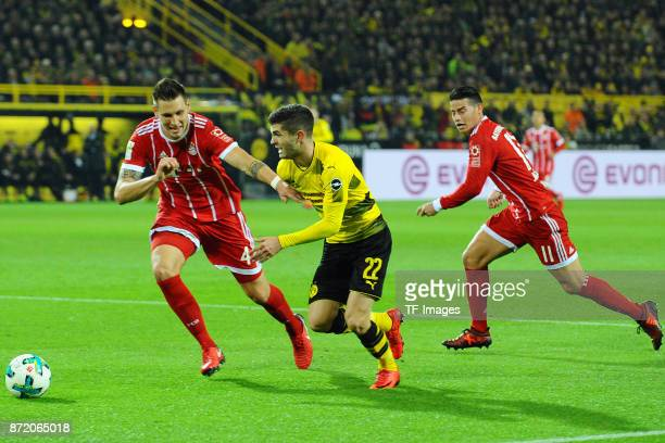 Niklas Suele of Bayern Muenchen Christian Mate Pulisic of Dortmund and James Rodriguez of Bayern Muenchen battle for the ball during the German...
