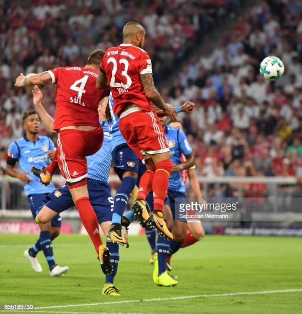 Niklas Suele of Bayern Muenchen scores the first goal of the match and the season covered by Arturo Vidal of Bayern Muenchen during the Bundesliga...