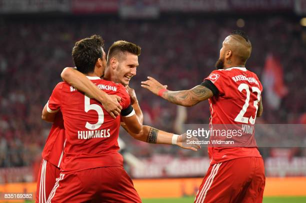 Niklas Suele of Bayern Munich celebrates scoring the first goal of the match and season with Mats Hummels of Bayern Munich and Arturo Vidal of Bayern...