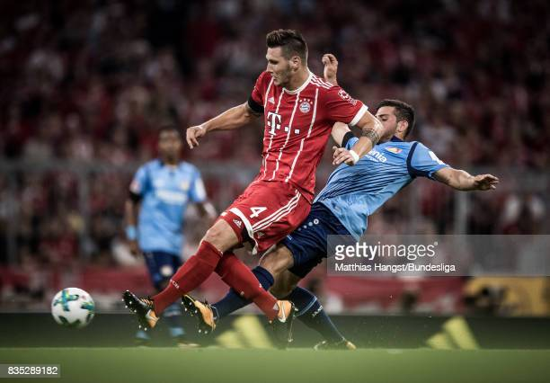 Niklas Suele of FC Bayern Muenchen is challenged by Kevin Volland of Leverkusen during the Bundesliga match between FC Bayern Muenchen and Bayer 04...