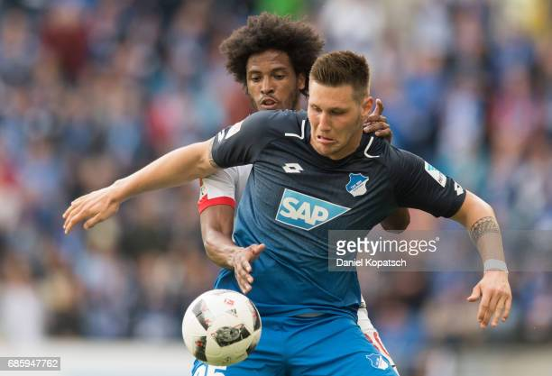 Niklas Suele of Hoffenheim is challenged by Caiuby of Augsburg during the Bundesliga match between TSG 1899 Hoffenheim and FC Augsburg at Wirsol...