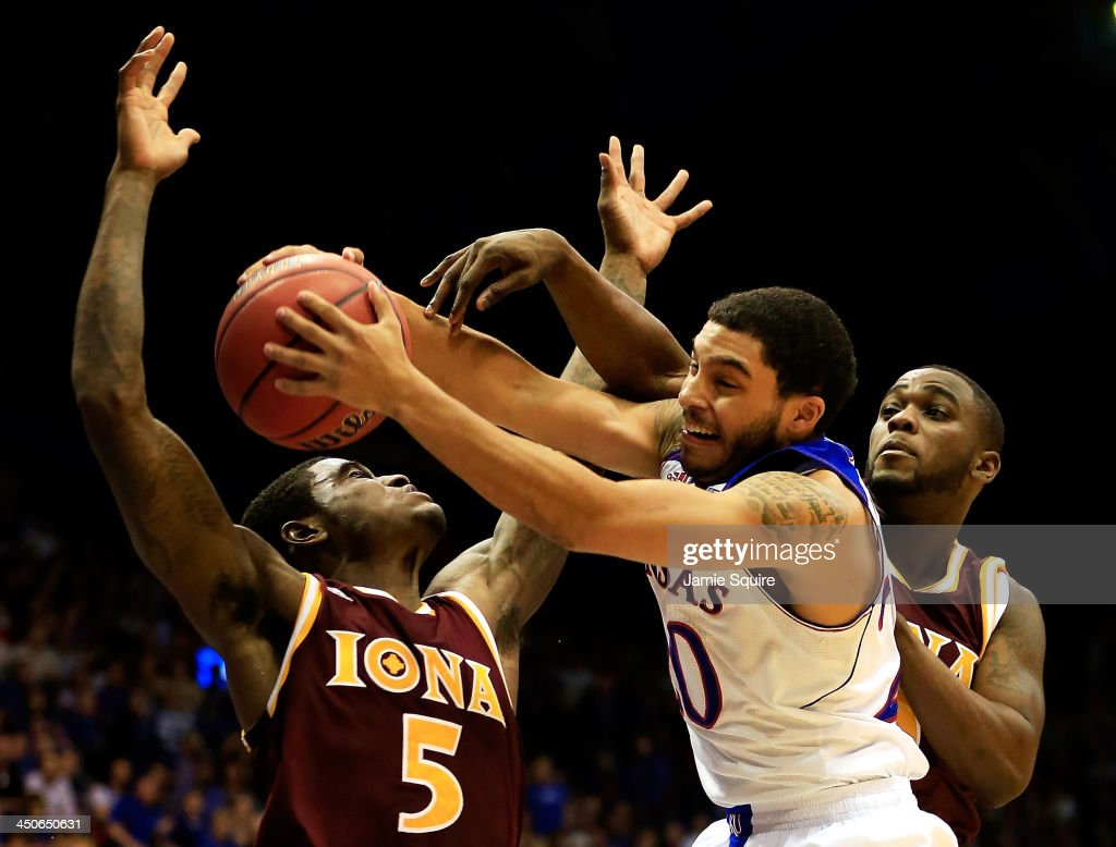 Niko Roberts of the Kansas Jayhawks battles AJ English and Deshawn Gomez of the Iona Gaels for a loose ball during the game at Allen Fieldhouse on...
