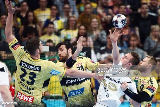 Nikola Bilyk of Kiel is challenged by Gudjon Valur Sigurdsson Gedeon Guardiola and Hendrik Pekeler of RheinNeckar Loewen during the EHF Champions...
